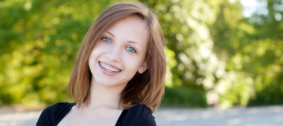 A smiling adolescent with braces representing the services of orthodontist Byrd Adkins D.D.S. Smile Company in Amarillo, TX